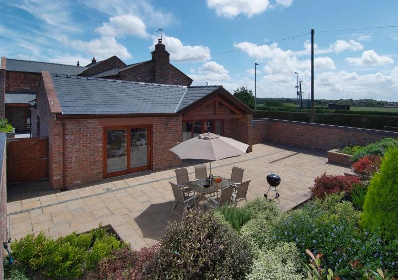 Private walled and gated patio with raised borders with stylish patio furniture and BBQ