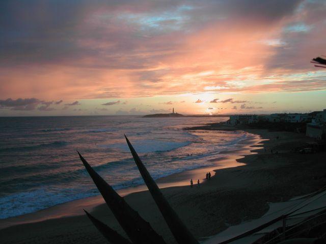 Puesta de Sol en la playa de Caños con el Faro de Trafalgar al fondo.