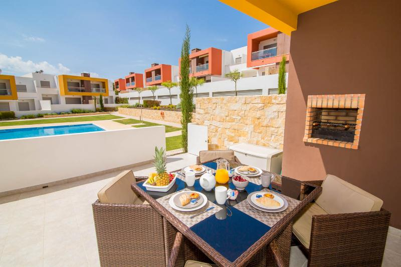 Sunny terrace with charcoal barbecue overlooking the pool and landscaped gardens