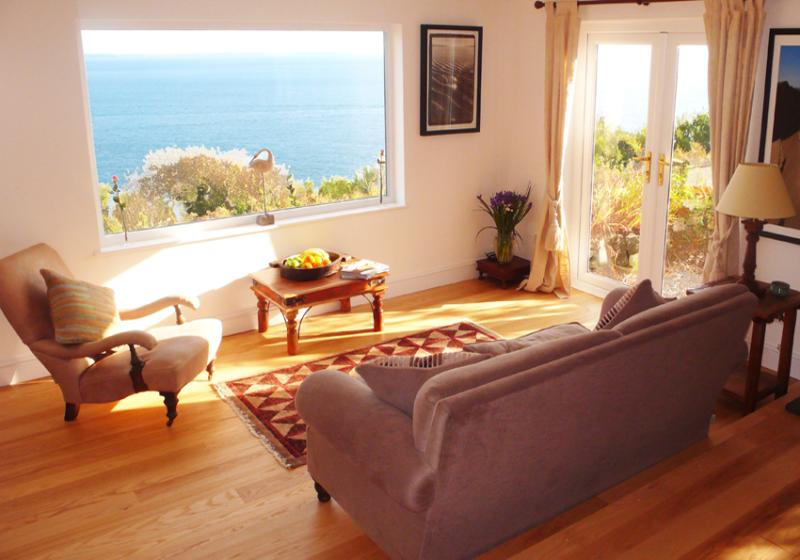 Sunny open plan sitting room with large window looking out to sea, and french doors to small terrace