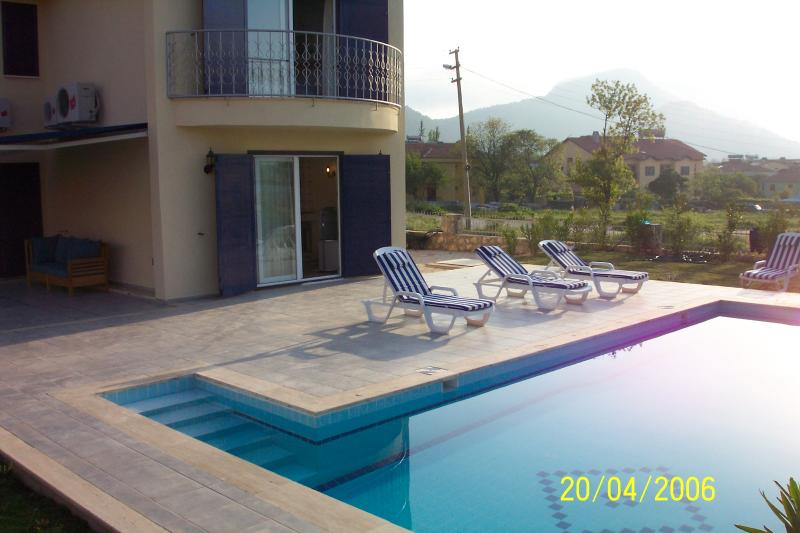 Beautiful private swimming pool with sunny terrace and pool furniture