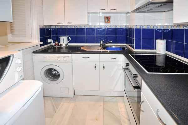 Kitchen with ceramic hob, full oven, microwave, fridge/freezer, extractor fan, washing machine.