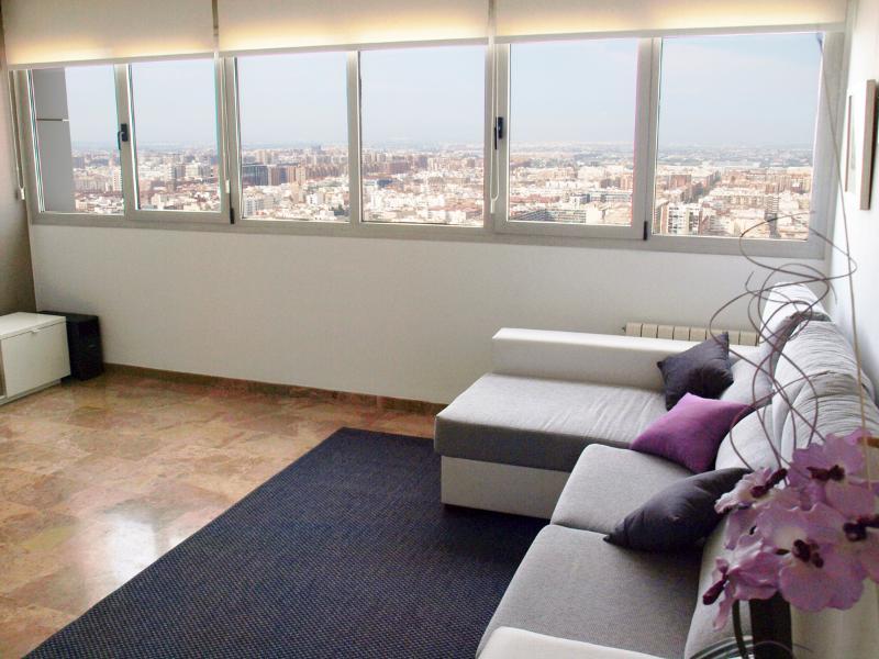 Salón con espectaculares vistas sobre la ciudad. Living room with spectacular views on the city