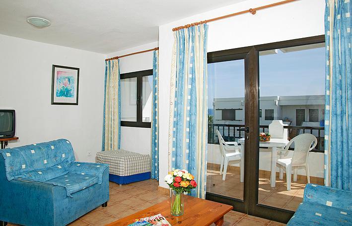 Sala conduce al balcón con vistas al mar y playa.