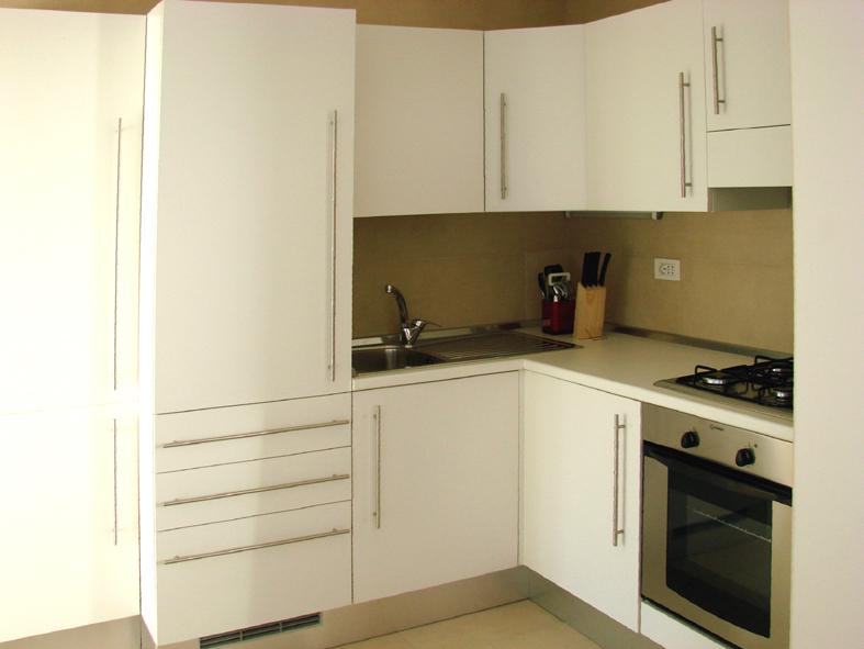 Kitchen with 4 gas rings and electric oven, fridge with freezer and washing machine