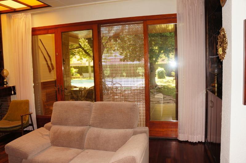Salón con la terraza y la piscina de fondo