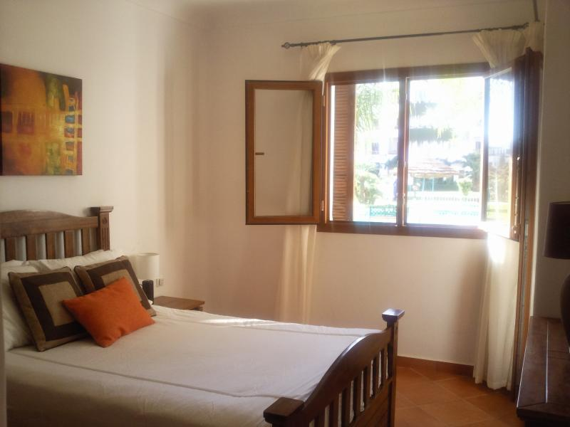 Double bedroom, fitted robes, air conditioning and door onto patio