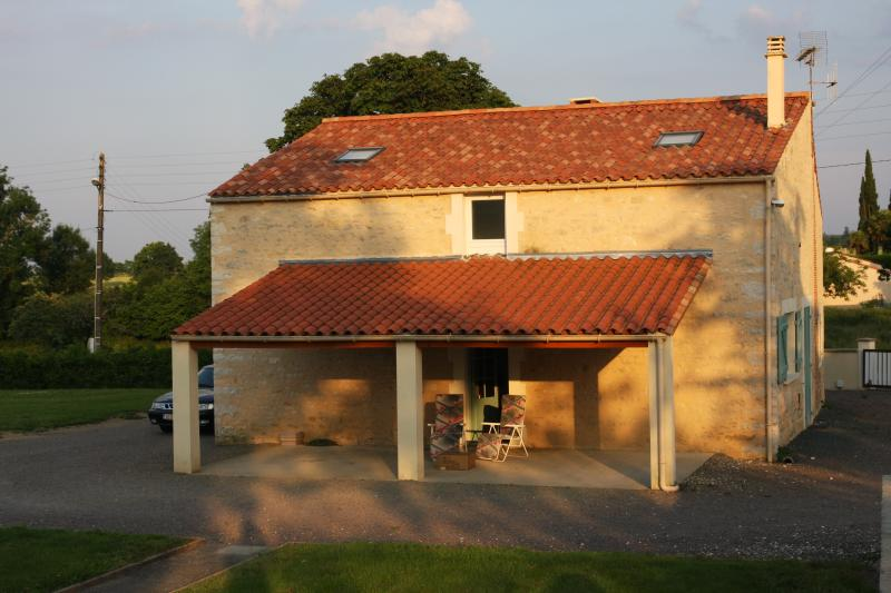 Le Paradis rear aspect with patio catching the evening sun, barbeque, table and chairs for 8