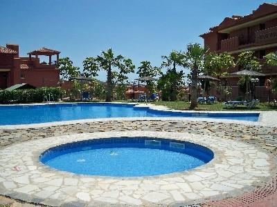 piscine de détente avec transats et parasols juste à l'extérieur de l'appartement.