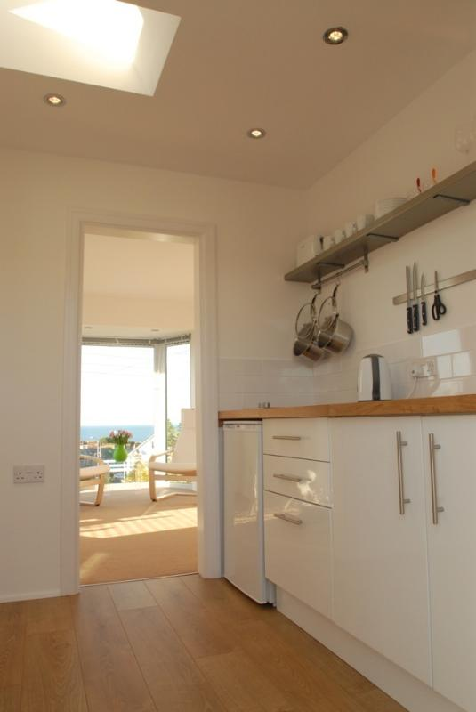 View from entrance through kitchen to living/bed room area and sea view beyond