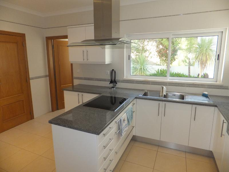 Large modern kitchen with separate utility room.  Views to private garden behind villa.