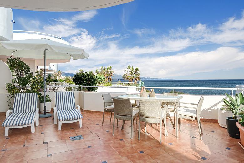 Balkong matbord och 6 stolar visar magnifik havsutsikt.