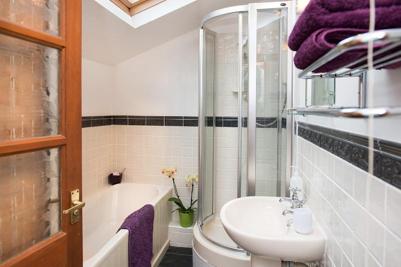 Holiday apartment bathroom with bath and shower