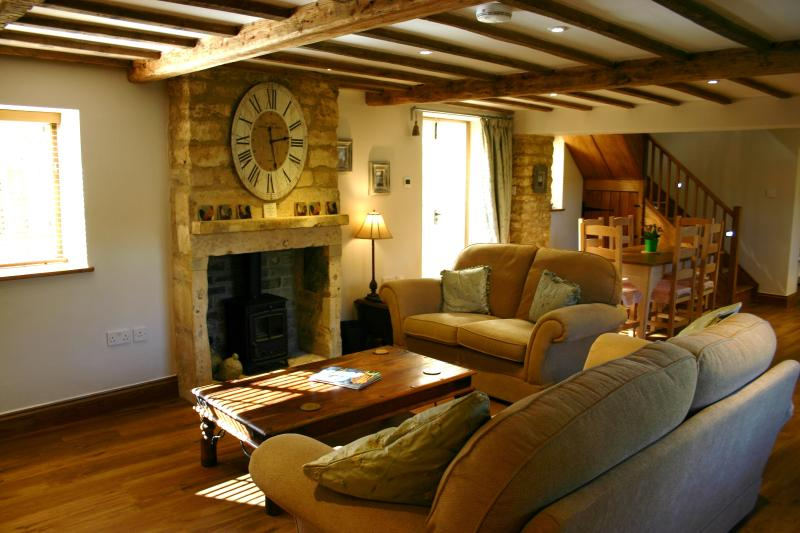 Sitting room with sofas, TV and a delightful little log burner
