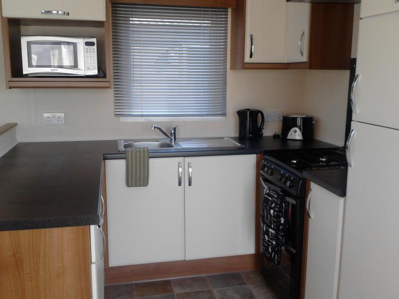 Modern fitted kitchen with gas oven, full size fridge freezer and microwave