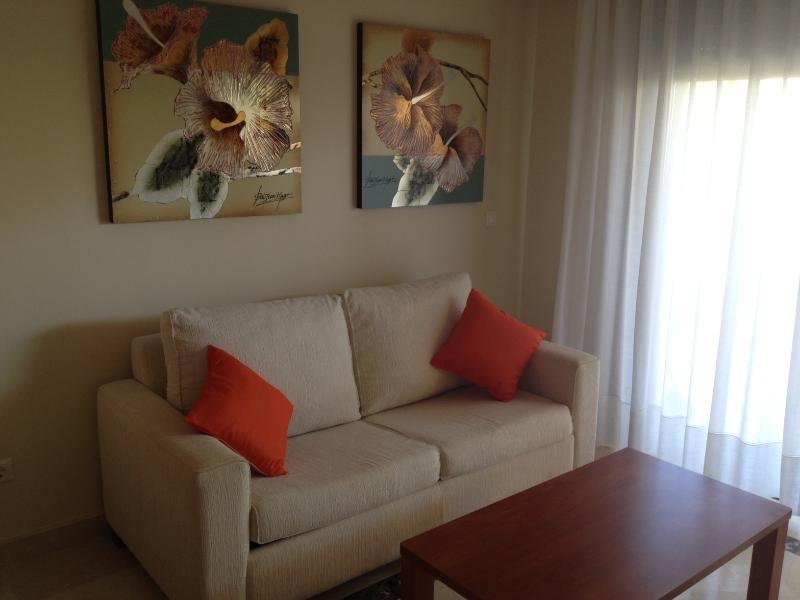 Sala de estar com portas de pátio para o terraço e um sofá-cama duplo