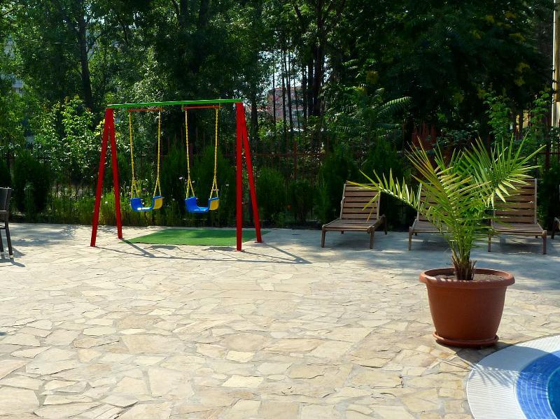 Balançoires pour enfants entre piscine et Bar