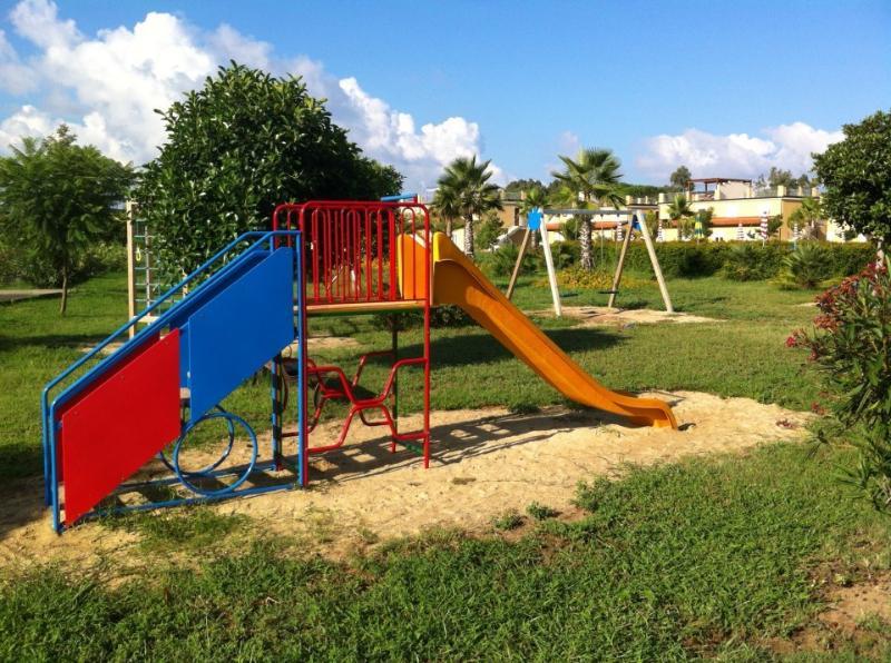 Parque infantil com baloiços, escorrega e frame de escalada