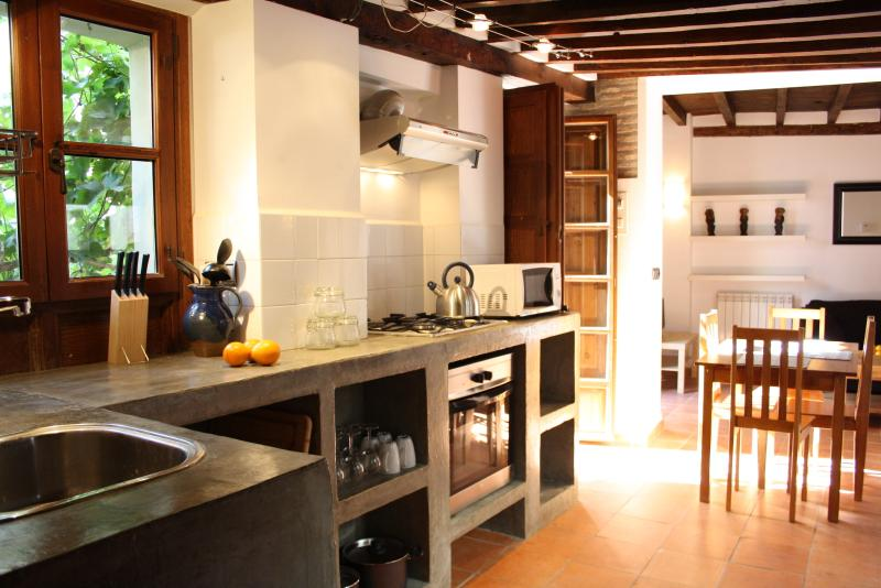 fully equiped polished cement kitchen with kettle, toaster, oven, microwave etc
