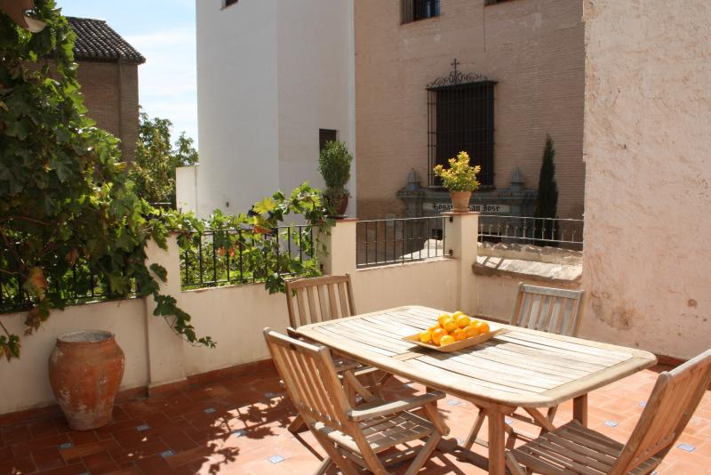 spacious south facing terrace with outdoor furniture for dining or enjoying sun.