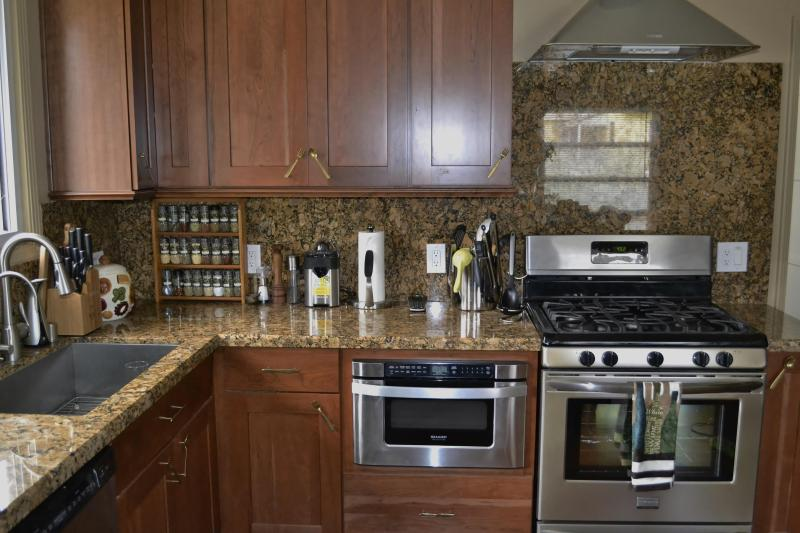 Sink on left, Thomasville cabinets, granite counter & backsplash, stove & range hood, microwave