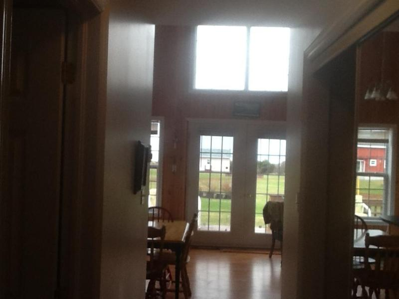 View from Hallway coming out of downstairs Bedroom. Washer in dryer behind glass doors