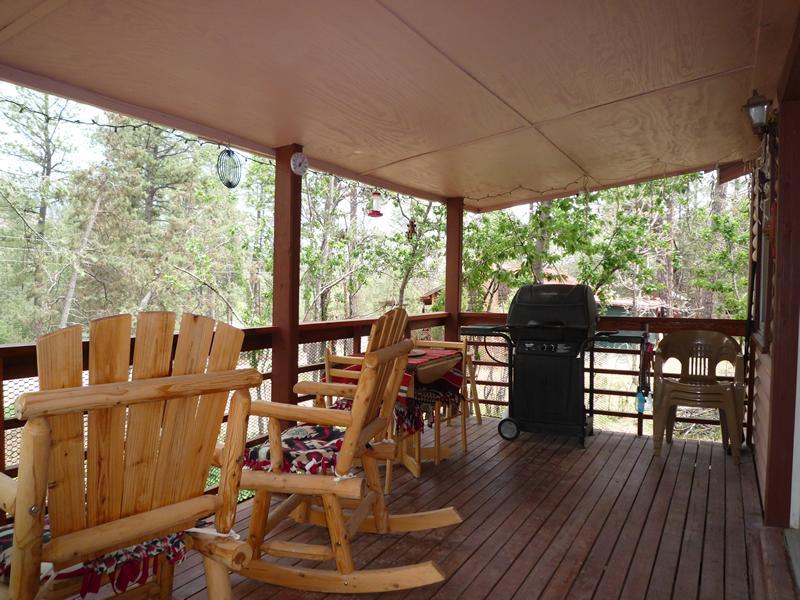 veranda coperta con sedie a dondolo e grill a gas