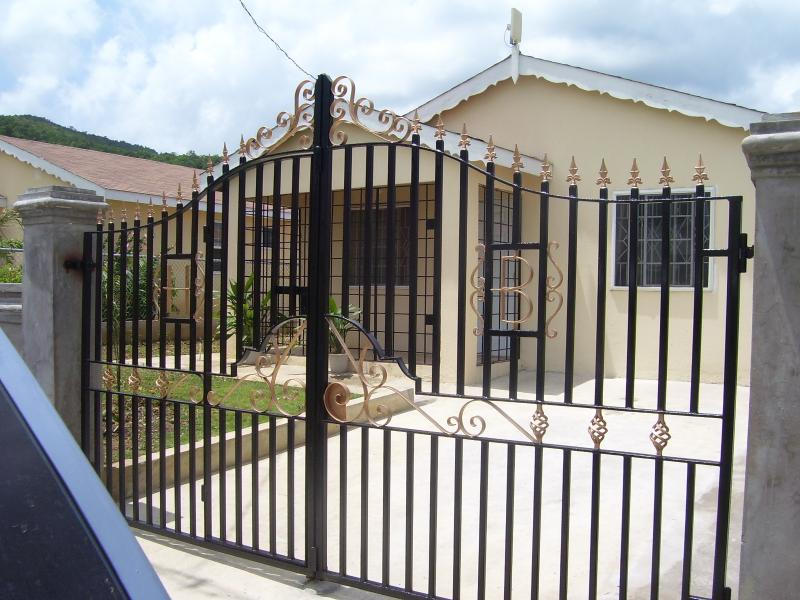 The front entrance with wrought Iron gates, secure parking and flower garden.