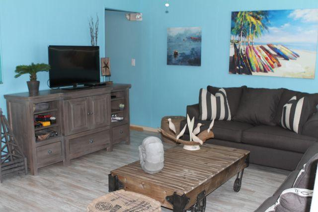 Living Room 'A' side shows the coastal pine floors found in both units and the fun artwork thru out