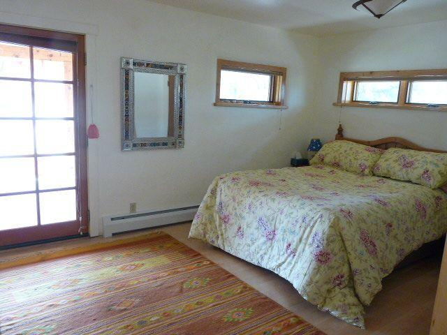 guest room with Mexican rugs and mirror opens onto front porch