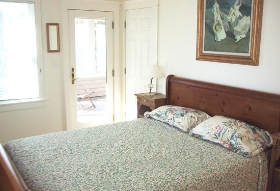 Anteriore destra camera da letto: camera da letto matrimoniale, letto queen size, vista oceano, ventilatore a soffitto e un portico dorme