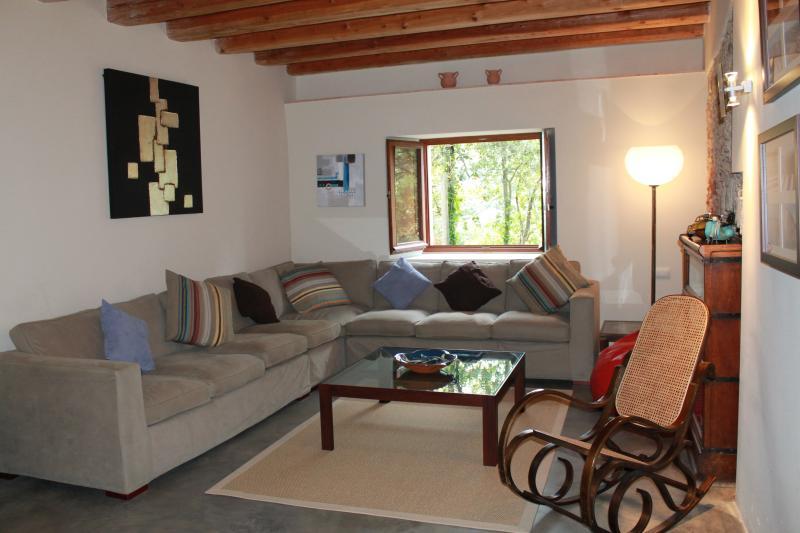 Sala com sofá para 12, sacos de feijão, cadeira de balanço. DVD e TV e biblioteca de área