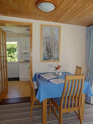 Il tavolo da pranzo nel salotto con spaziosa cucina oltre