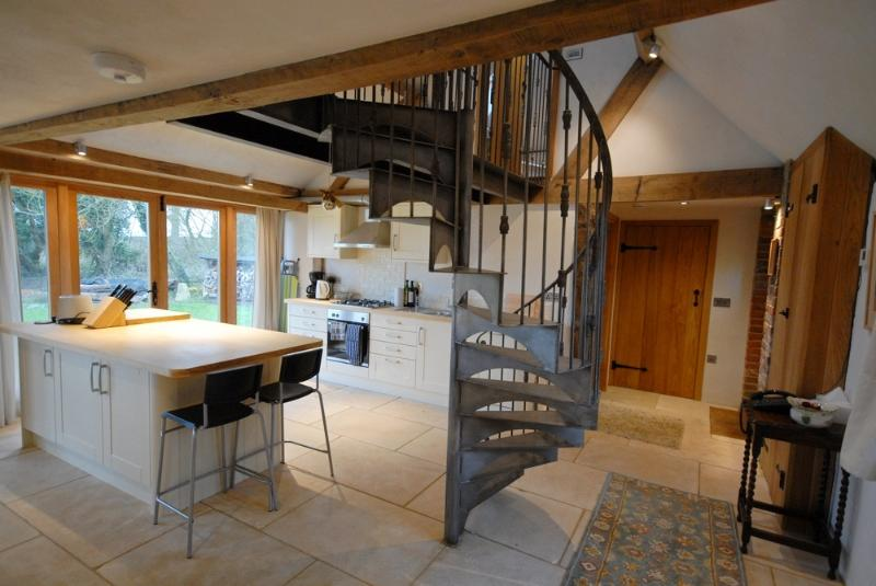 Kitchen with breakfast bar and bespoke spiral staircase