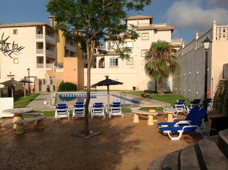 The swimming pool to the side of the apartment with loungers.