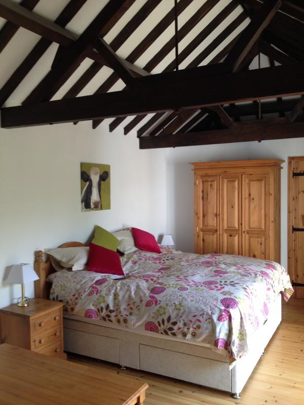 Master bedroom with beams, and en-suite with patio doors to garden