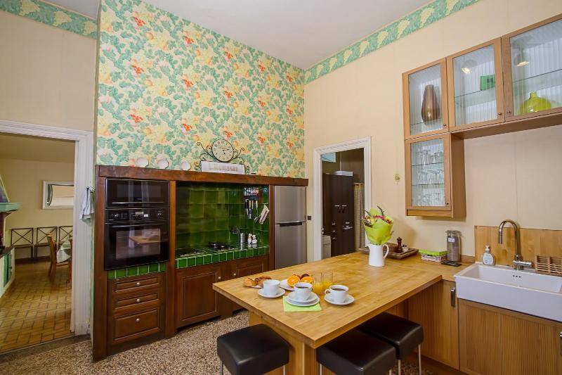 Kitchen includes a dishwasher, four-burner stove, oven, microwave, and large refrigerator.