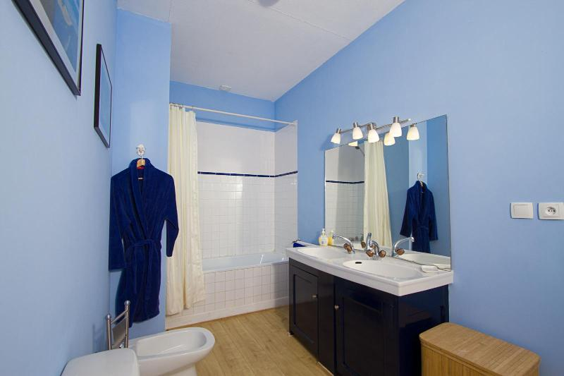 Bathroom shared by green and blue bedroom has double sinks. Fluffly cotton robes provided.