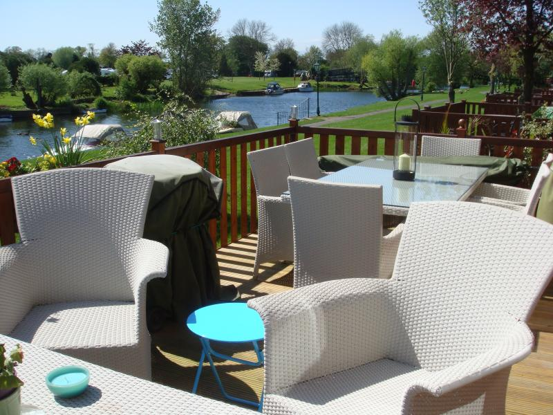 River views from decking with sofa seating and 6 seater dining table plus barbeque