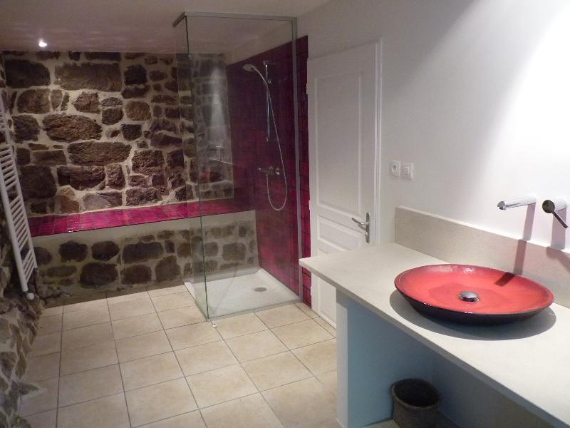 Salle de bain en pierre et verre avec vasque céramique faite main