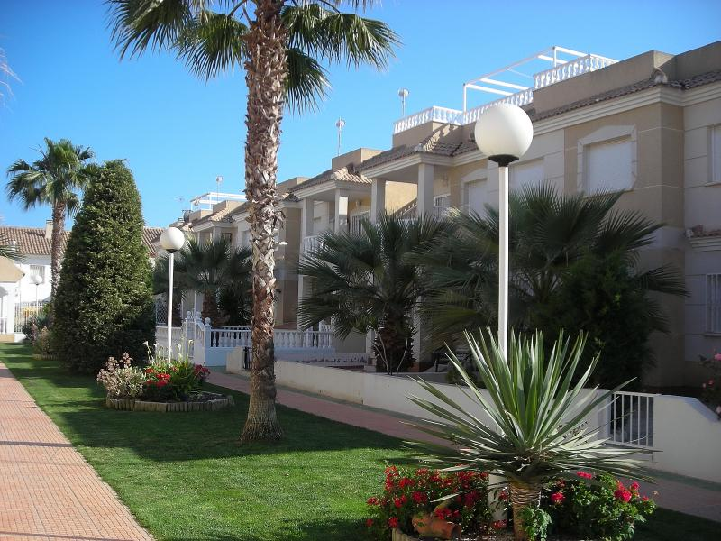 View of the apartment (first floor - centre, right of the central palm tree) and gardens