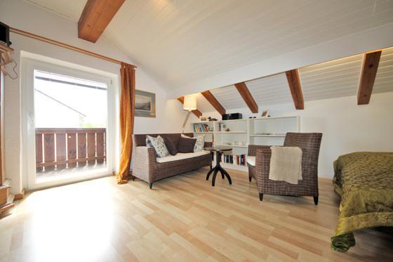 Gemütlicher Wohnbereich mit Sofa, Sessel & Literatur