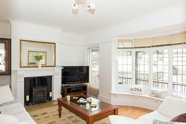 Beau salon avec de nombreux sièges pour six avec une grande baie vitrée et le siège de la fenêtre