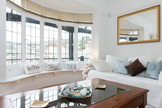 Une belle chambre avec une grande baie vitrée et le siège de la fenêtre