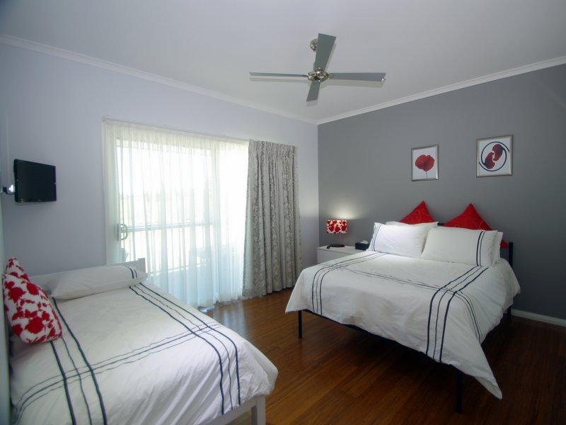 Bedroom 2 with double single beds,  built-in wardrobe and TV.