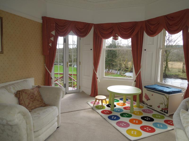 Play area in lounge with doors to balcony - views onto garden and river.