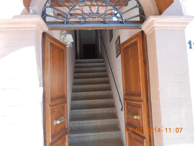THE DOOR IS OPEN WITH A VIEW OF THE ENTRANCE STAIRCASE READY TO ACCOMMODATE GUESTS