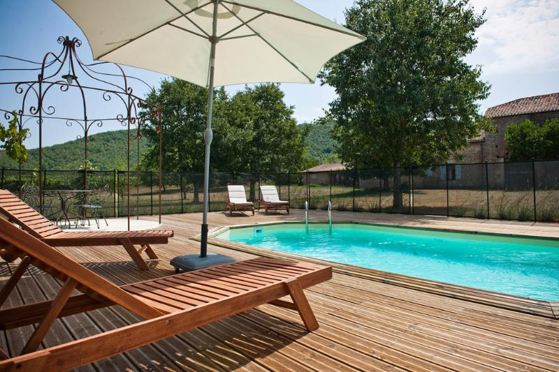 Heated swimming pool with sun loungers and beach towels