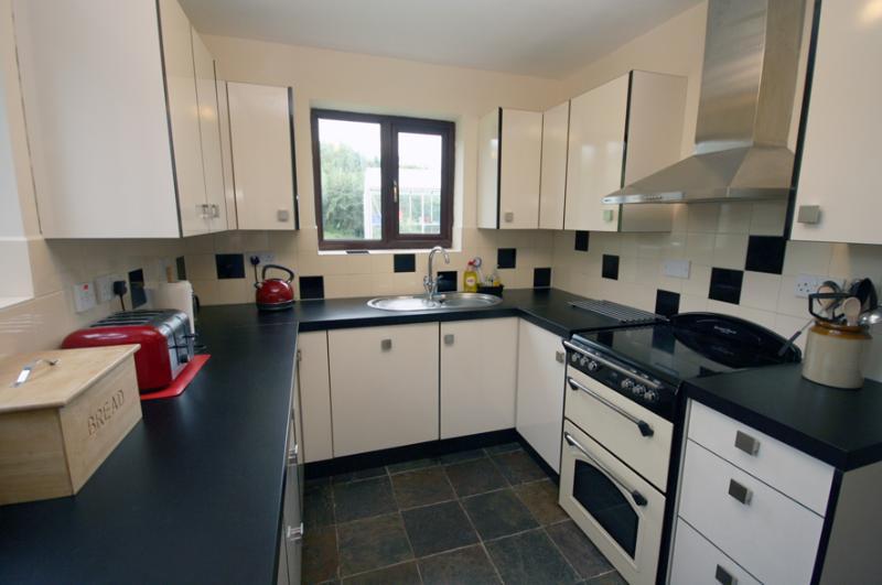 Cocina elegante y bien equipada con cocina superior de cerámica, lavavajillas, nevera, congelador y microondas.