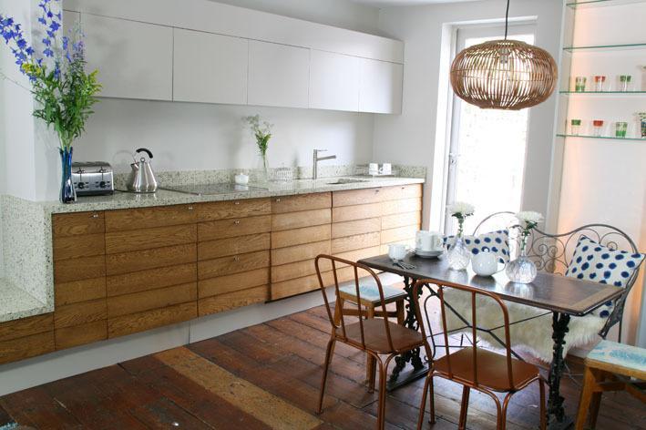 Handmade open plan kitchen/diner. Door out to glass balcony patio